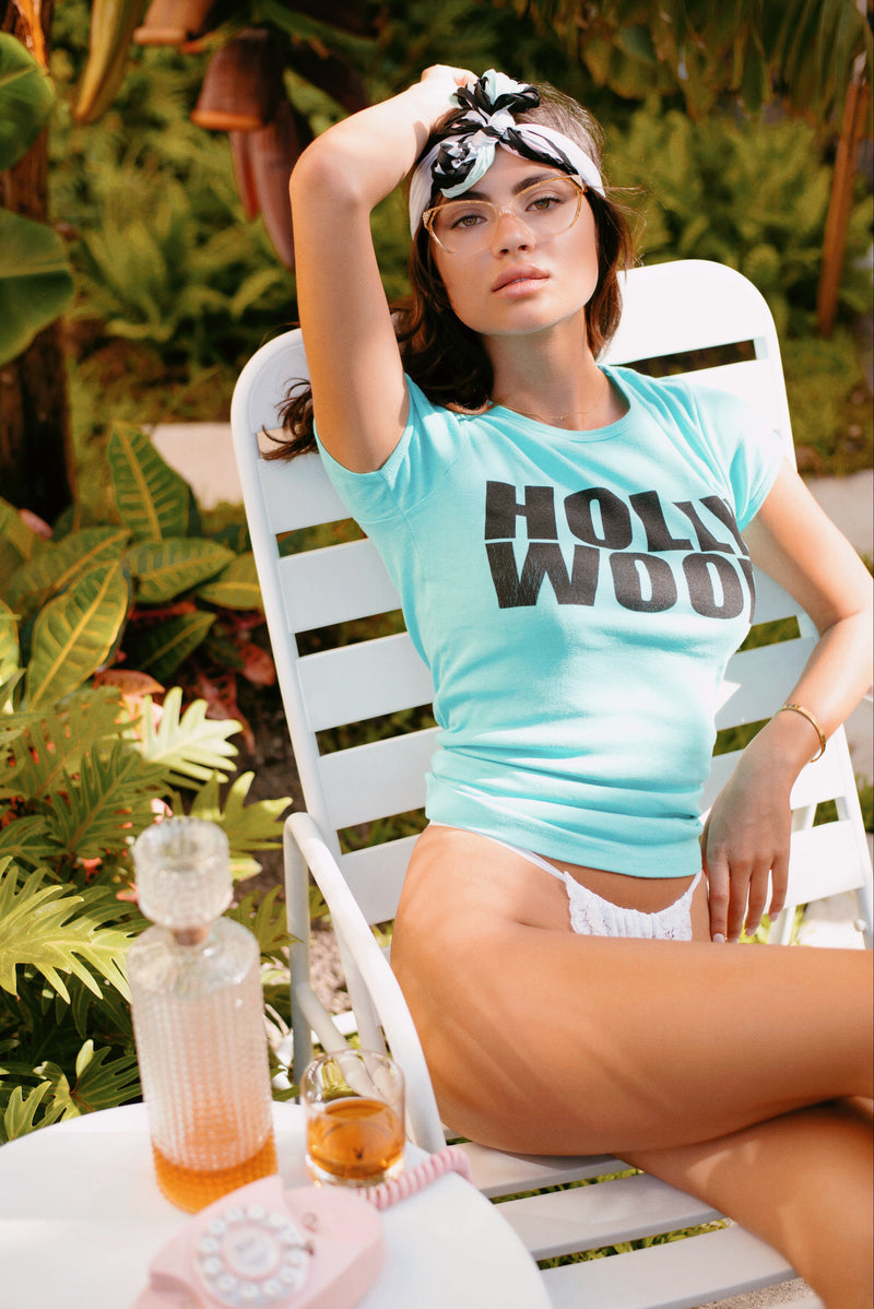 Female model wearing teal shirt that reads Hollywood.  The words Holly are on top of Wood.