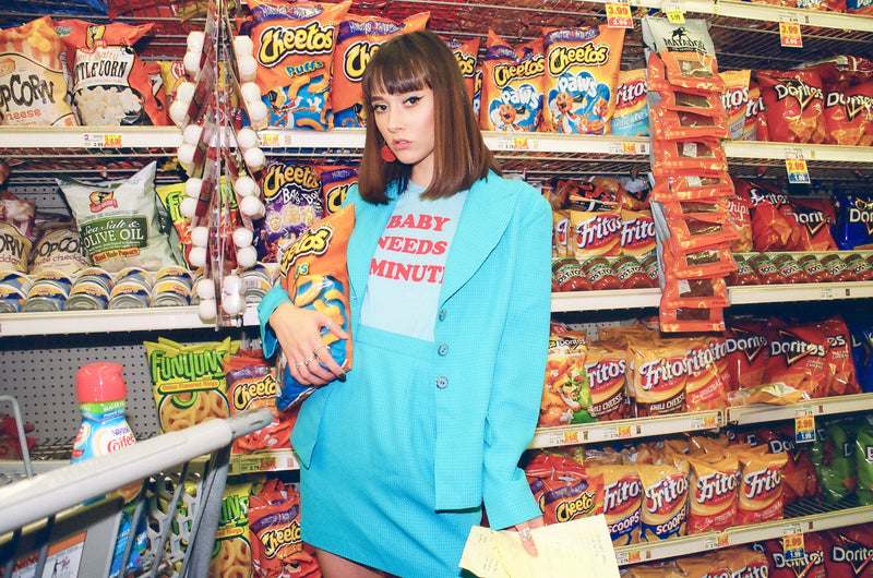 619f4deb7 Girl in supermarket wearing blue vintage 70s t-shirt. Baby Needs a Minute  ...