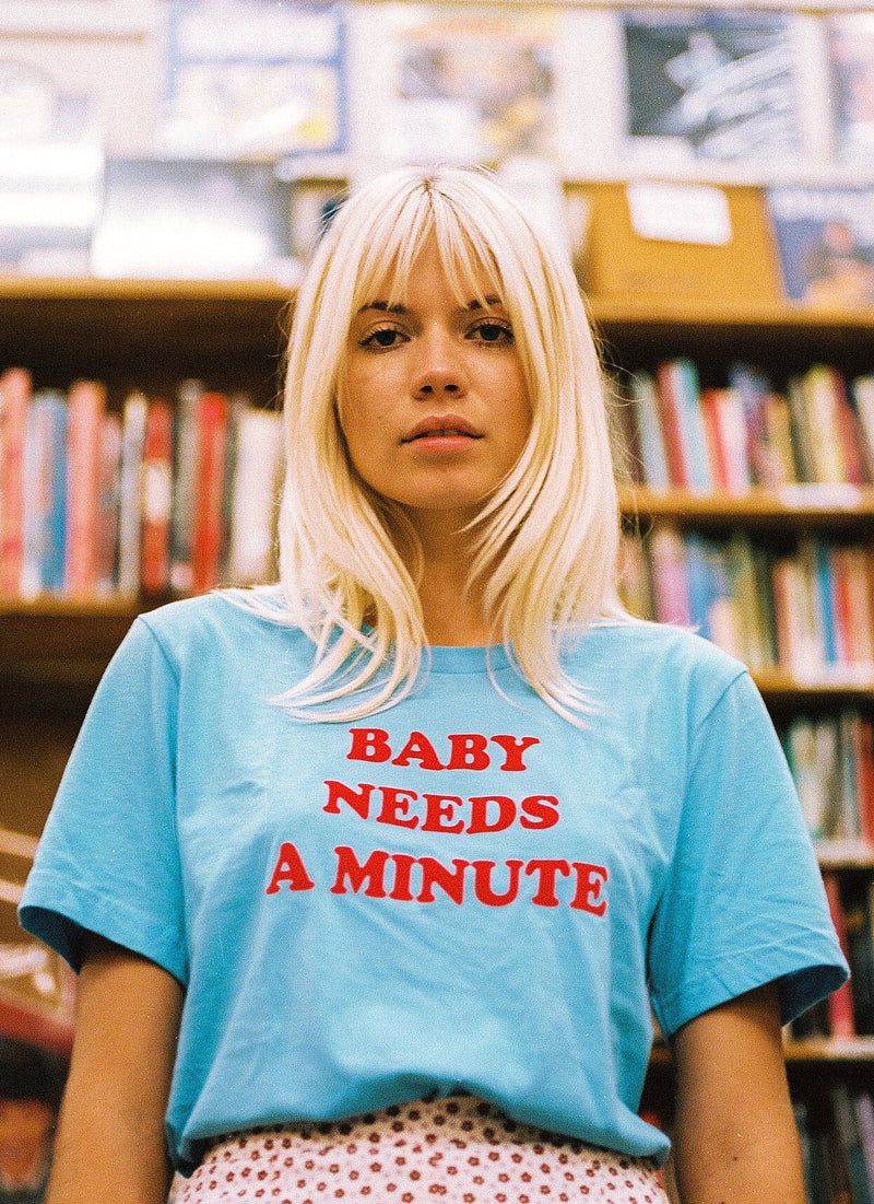 Girl in library wearing baby blue 1970s women's graphic t-shirt