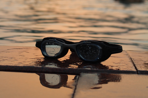 Swimming goggle on the side of the pool