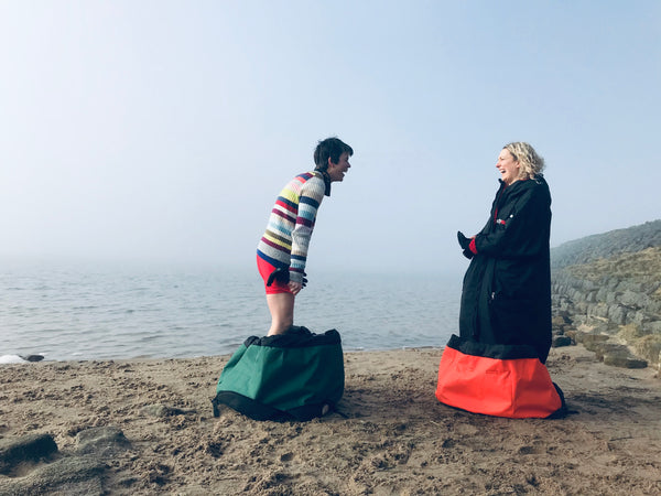Two people each standing in their Turtleback bags at the side of the water laughing