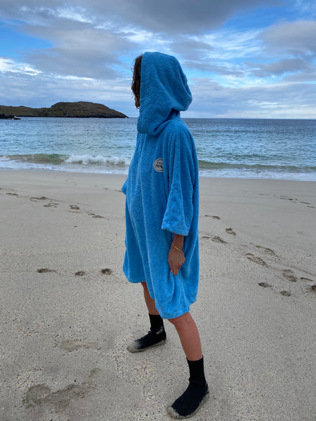 Person wearing a Swim Feral Towelling Poncho on the beach with neoprene socks on