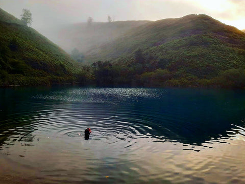 Lou Holmes swimming in a lake surrounded by hills