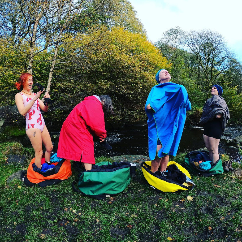 Jamima and swim friends standing in their Turtleback outdoor swim bags getting changed by the river