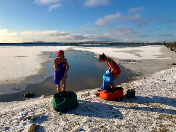 Two people getting changing in their Swim Feral Turtleback bags in the snow next to the water