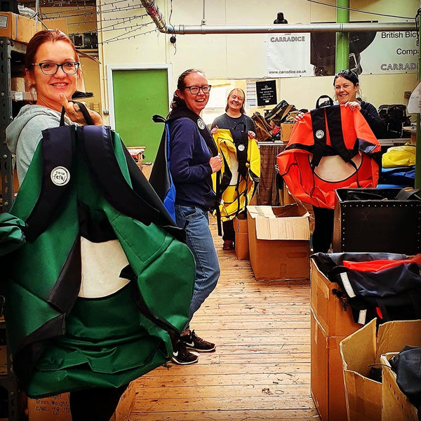 Staff at the factory looking at the camera and holding up the Turtleback bags they have made