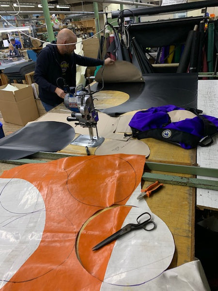 Larry tarp being cut into circles at the factory ready for a Turtleback bag