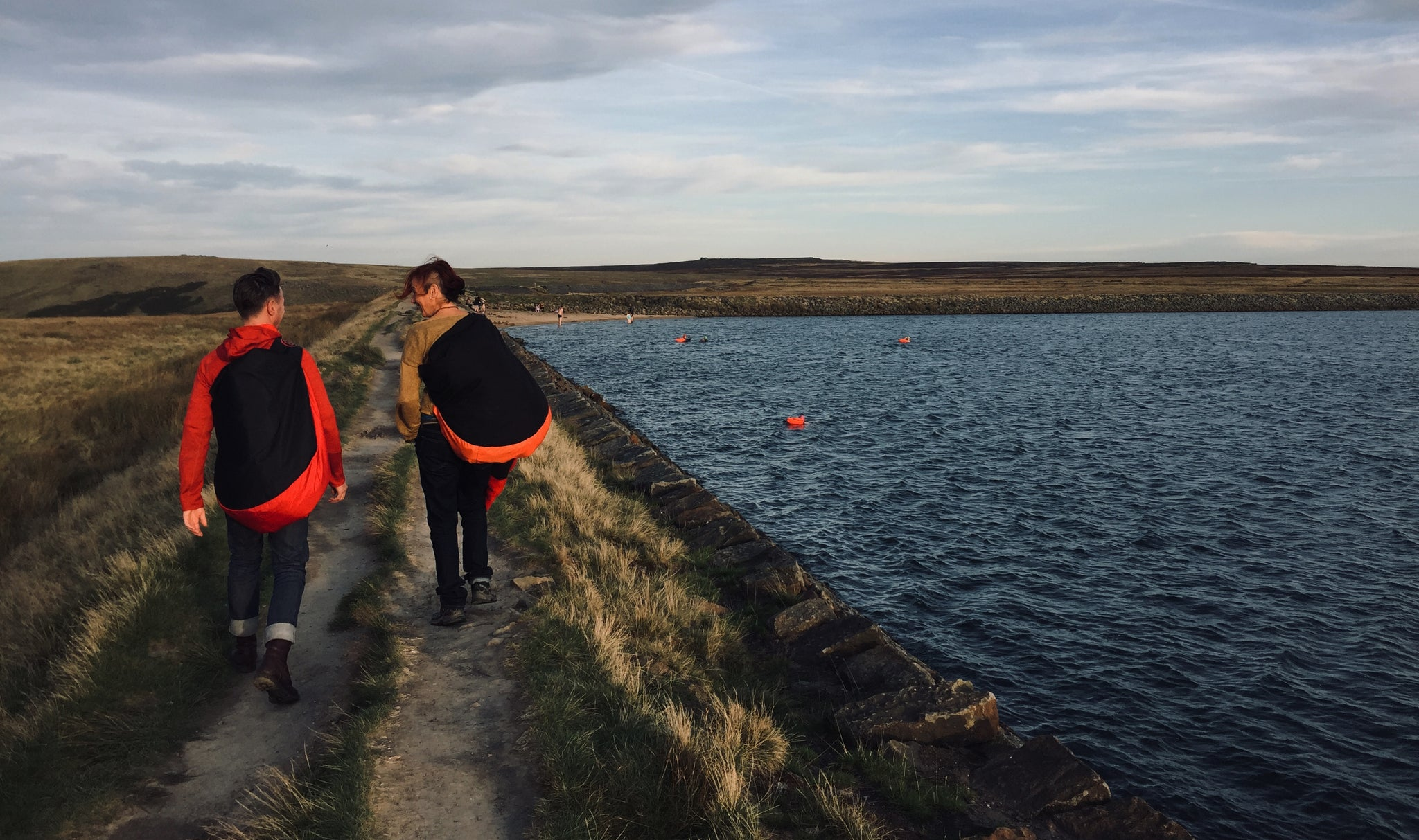 Noah and Jamima walking into the distance near some water with their Turtleback outdoor swimming bags on their backs