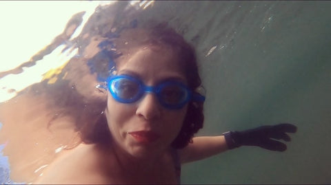 Mercedes underwater with goggles on looking at the camera