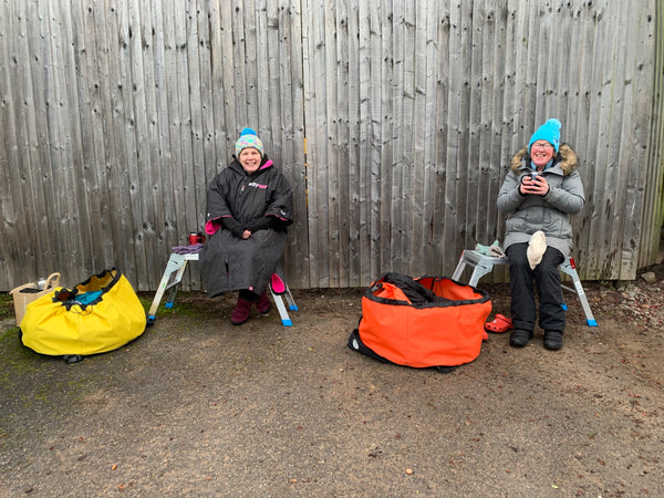 Judie and Kitty sitting next to their Turtleback outdoor swimming bags after a swim.