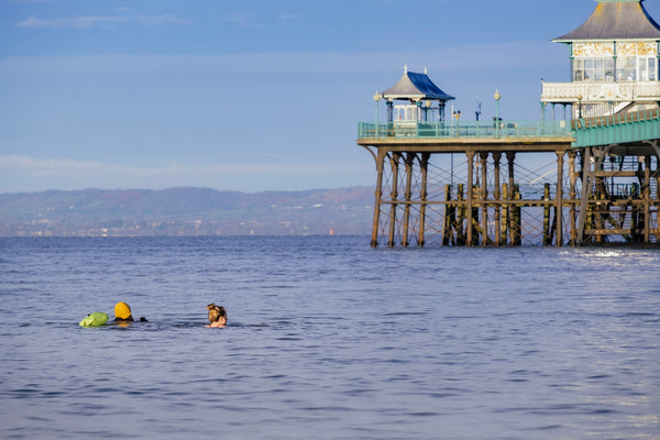 Shot of the sea with a pier on the right and Lauren and her friend's head bobbing away in the distance