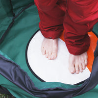 Picture of a woman feet on the insulated mat inside the Swim Feral Turtleback swim bag