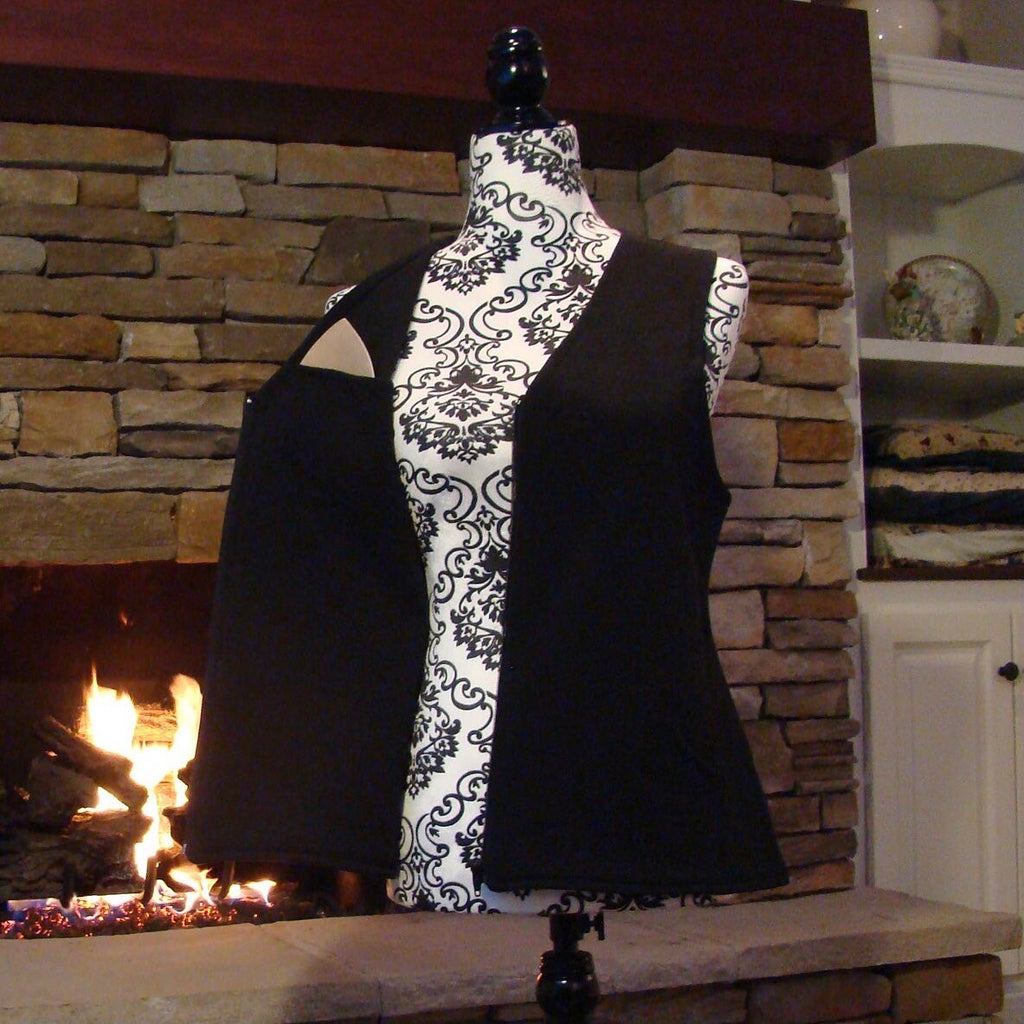 A black vest for women made in North America of 100% cotton is on a dressmaker's dummy placed infant of a fireplace. The vest is a breast prosthetic that is way more comfortable than any mastectomy bra.