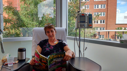 Women in hospital receiving chemotherapy while reading a magazine. She is Judy, inventor of the Best Breast Vest which is more comfortable than any mastectomy bra.
