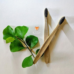 Two bamboo toothbrushes lying next to leaves.