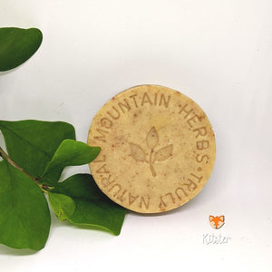 A round natural soap that is beige in color and has Mountain Herbs stamped on it