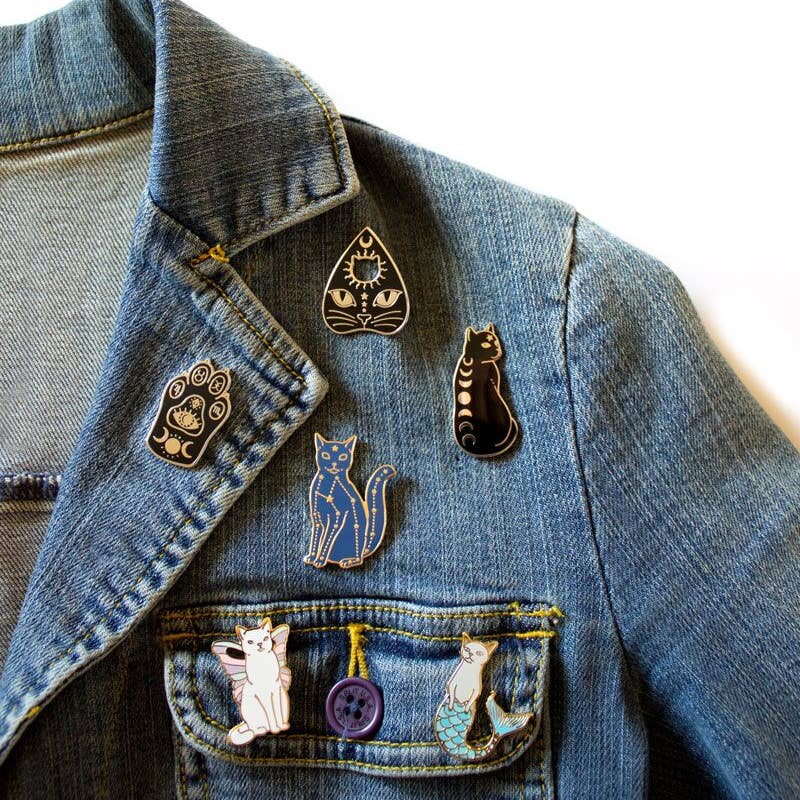 Denim jacket with an assortment of cat enamel pins