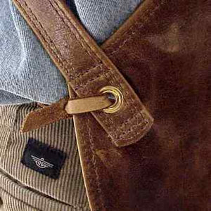 "Cross-back adjustable straps leather apron, edges are turned and sewn, leather thong tie at the waist. Size 28"" x 24.5"""