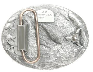 An exquisitely designed image of a bull rider surrounded by two feathers and lassoed by a rope around the outside of the buckle.  This beautiful antiqued buckle is made of fully cast metal by Siskiyou. Made in the USA, dated 1995.  The back of the buckle is designed and features 2 cow heads with horns.