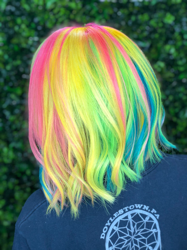 High fashion hair colour showing pink blue yellow green and purple hair