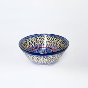 Small artisan stoneware serving bowl in red, green and blue hand-printed pattern