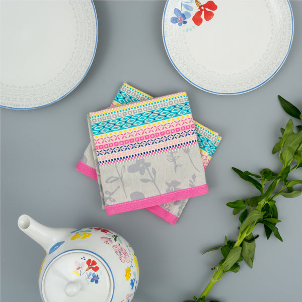 Woven cotton tea towel by Artisan Homeware in Grey anbd Pink beside floral teapot and plates