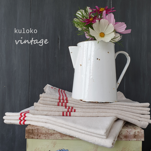 A large white enamel jug filled with fresh flowers is carefully placed on a small stack of vintage linen against a dark grey painted background with the words kuloko and vintage next to them.
