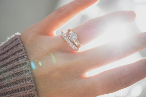 Diamond Engagement Ring on woman's hand with wedding ring