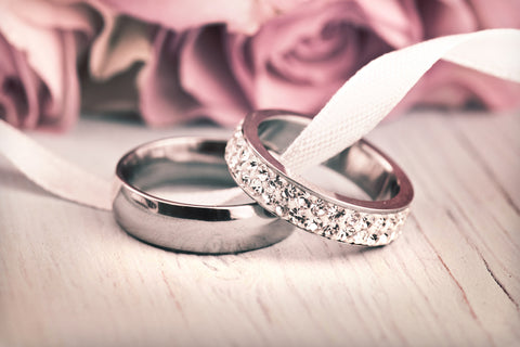diamond wedding rings with roses in background