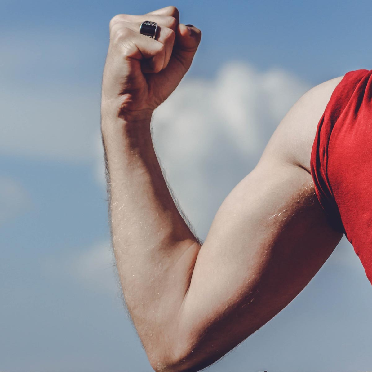 A man in a red t-shirt flexes the muscles on his right arm