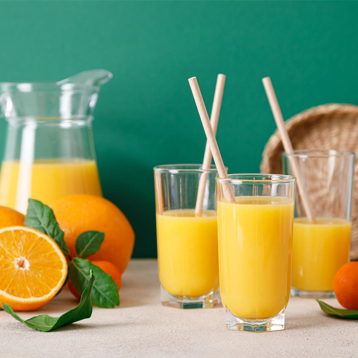 An electrolytes drink sits in glasses and a pitcher surrounded by fresh oranges