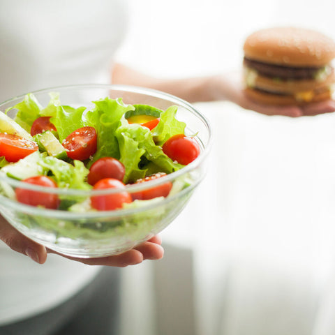 A woman holding a salad in one hand and a burger in the other, trying to outweigh which one is the better option
