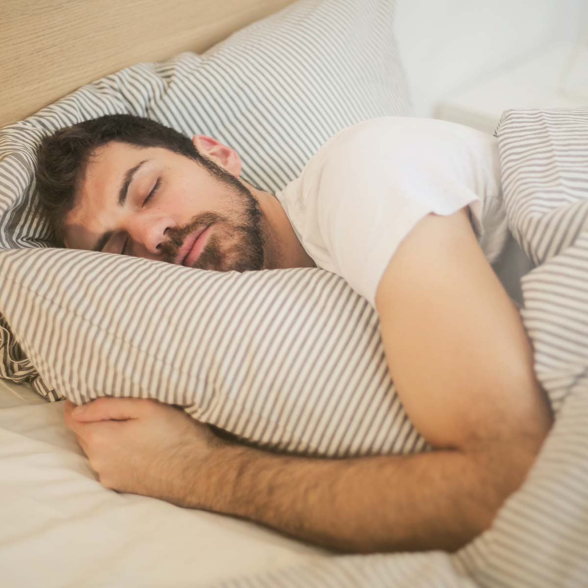 Man in a white T-shirt sleeps in a cozy, soft bed