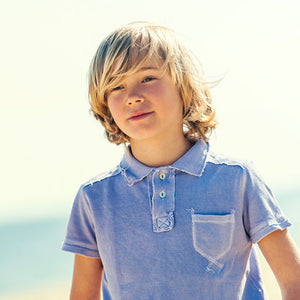 Young fashionable boy wearing a blue polo shirt outside.