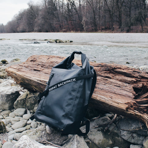 The backpack on a bicycle tour along the Isar - leaning against a washed-up tree trunk.