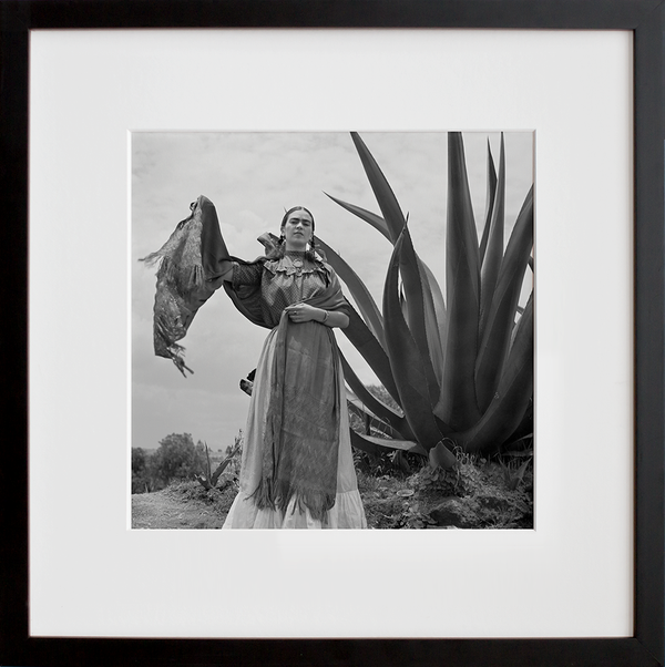 Frida Kahlo standing next to an agave plant