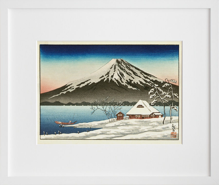 Winter landscape with small snow-covered building on the coast and view of Mount Fuji