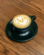 coffee drink in black mug on black saucer on wooden tabletop
