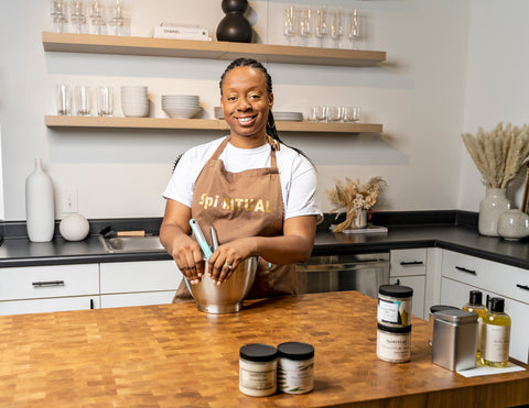 African American Woman standing in kitchen with mixing bowl and several products on the table