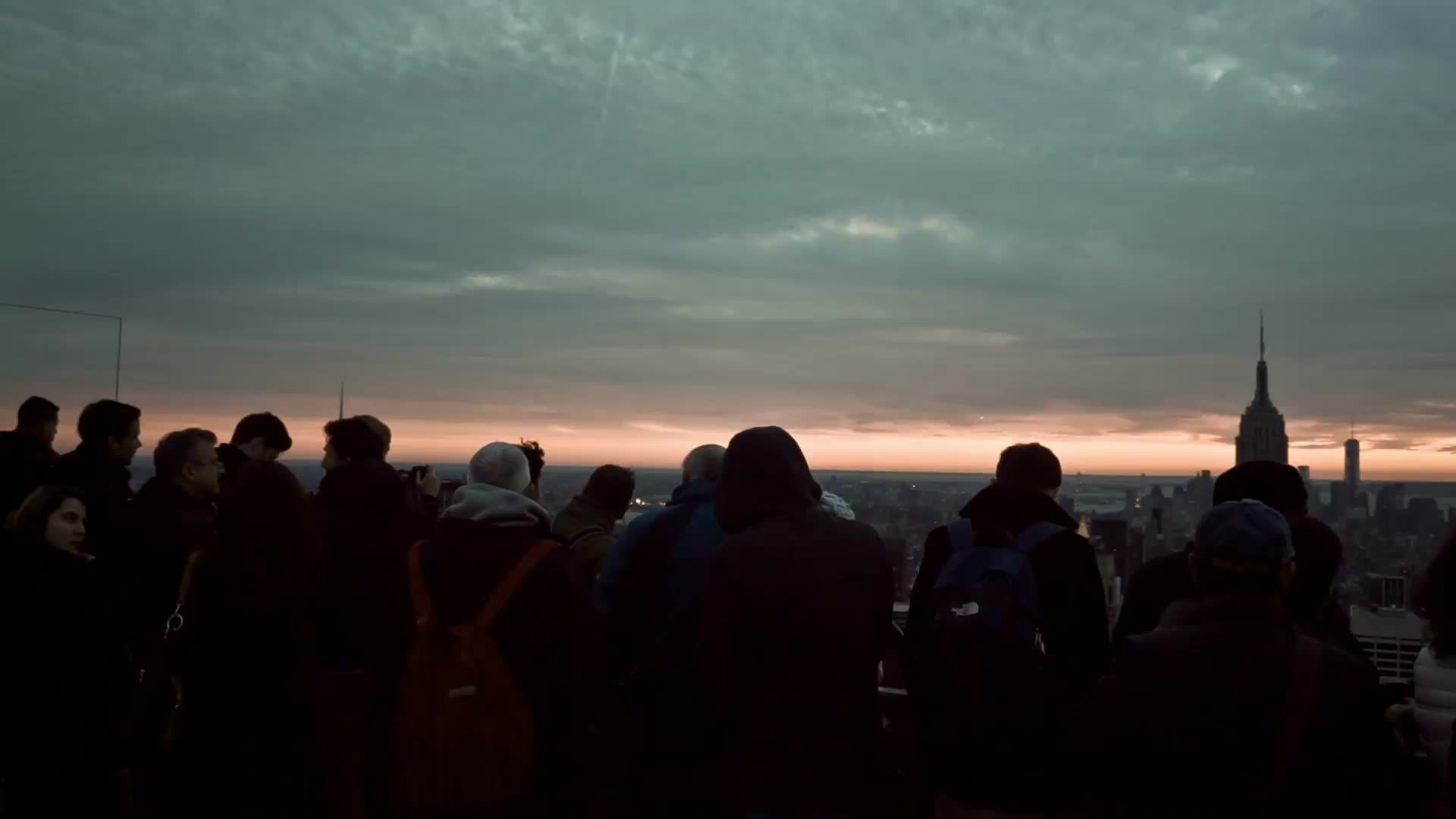 silhouettes of tourists looking at Manhattan cityscape from observation deck high up on chilly fall day at sunset in NYC