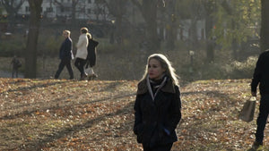 attractive woman in autumn walking through Central Park on cold fall winter day with trees and leaves on ground, slow motion