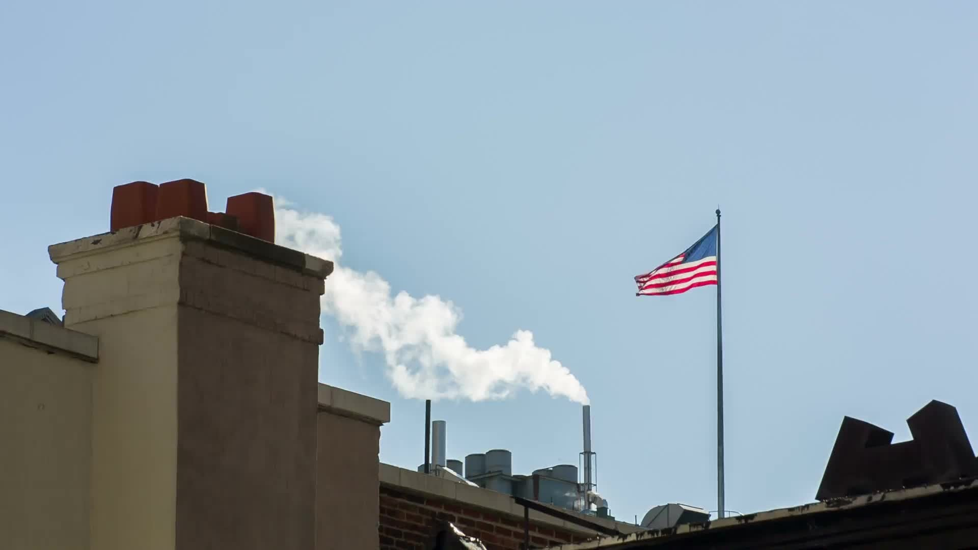 American flag on rooftop with steampipe blowing smoke in New York City