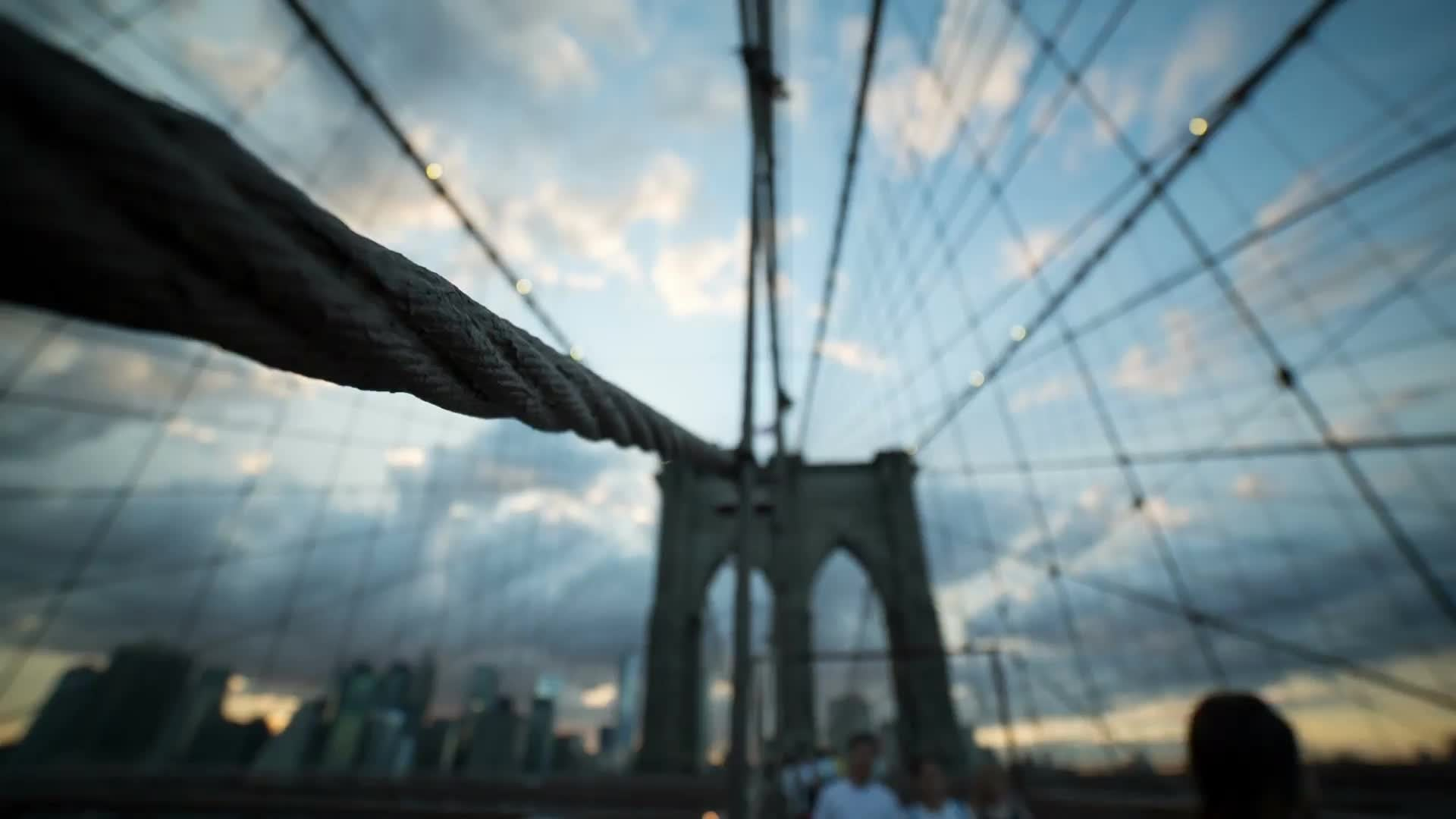 Brooklyn Bridge close-up of suspension cables, people crossing on pedestrian walkway at sunset with Manhattan skyline