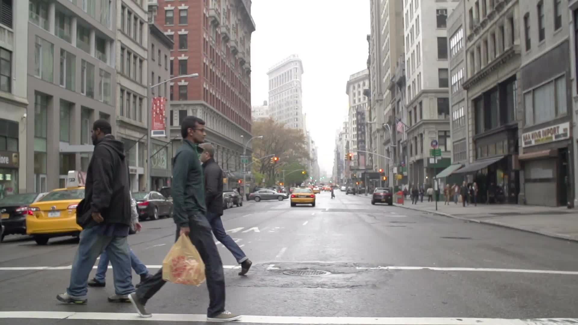 people crossing 5th Ave with Flatiron Building in background on muggy fall day in Manhattan NYC
