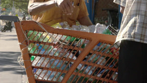 closeup of hand sorting dirty cans in shopping cart on street on sunny summer day - recycling in NYC