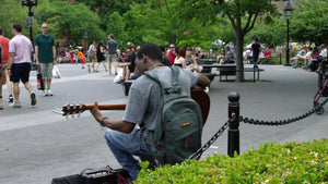 musician playing guitar in Washington Square Park on summer day in Manhattan NYC