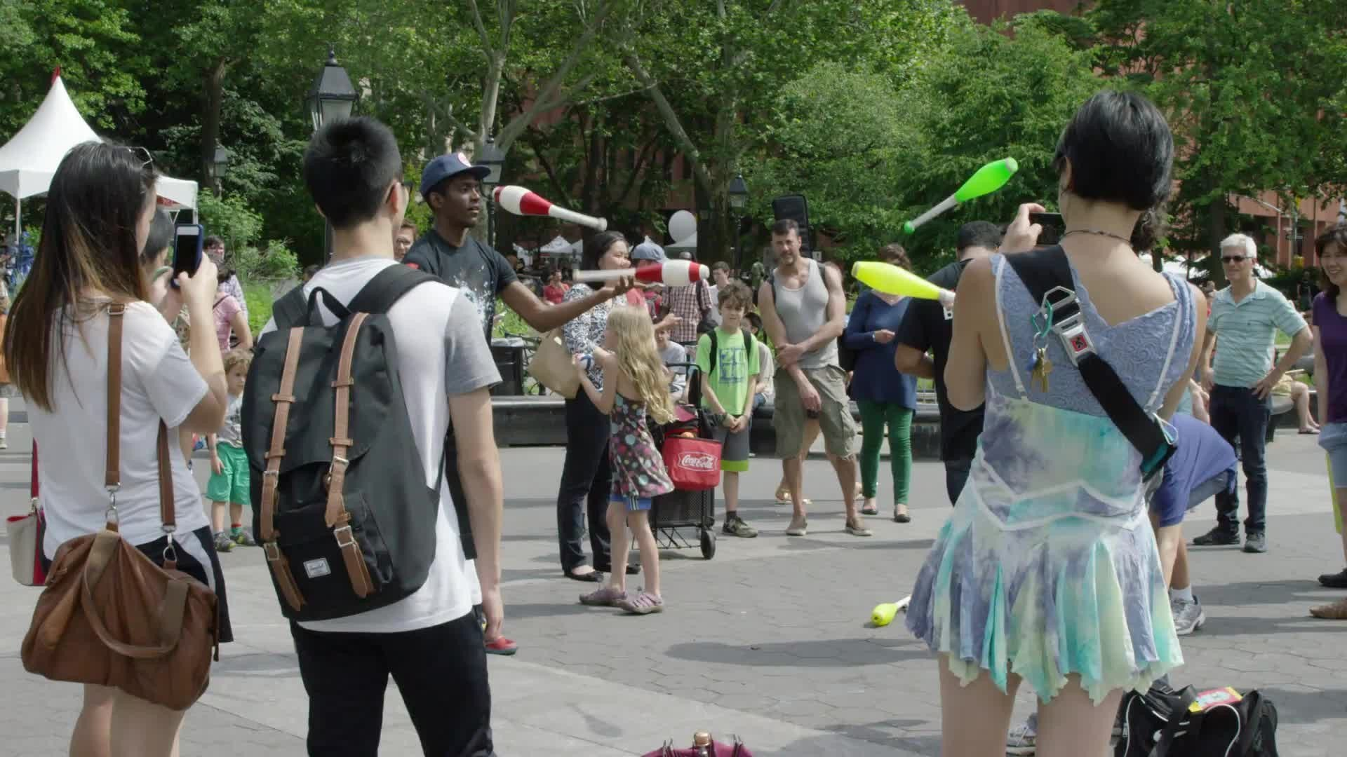 jugglers performing in Washington Square Park in summer - juggling bowling pins in slow motion