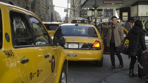 tourist getting into taxicab at taxi stand outside Penn Station on fall day in Manhattan NYC