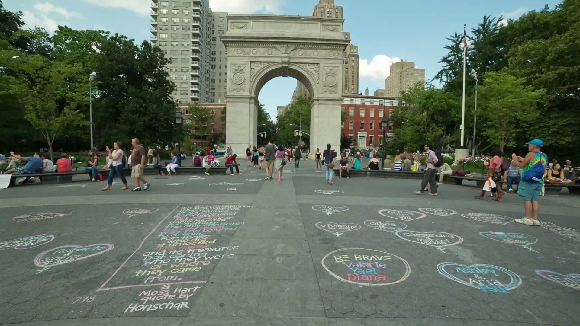 chalk art and writing on ground in Washington Square Park with arch and people on summer day in NYC