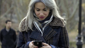 beautiful woman text message on smartphone in Central Park on cold fall winter day, in coat and scarf